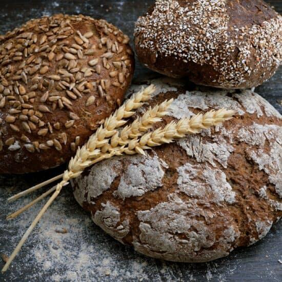 3 Vollkornbrote mit 3 Weizenehren auf dunkler Holzplatte mit Mehl