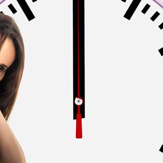 Frau sitzt deprimiert zwischen vielen Uhren im Hintergrund