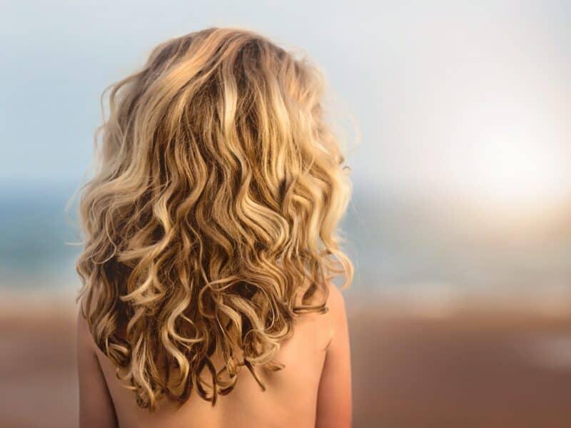Blonde gelockte Haare einer Frau von hinten